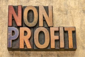 nonprofit banner - word abstract in vintage letterpress printing blocks stained by color inks against bark paper